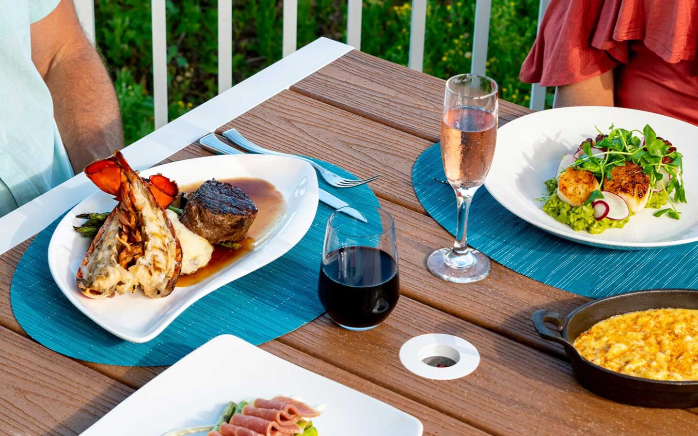 Glass of champagne, red wine, lobster dish and salad