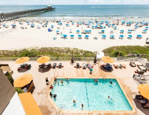 view overlooking hotel pool, beach full of umbrella chaise lounge chairs and boardwalk to pier over water