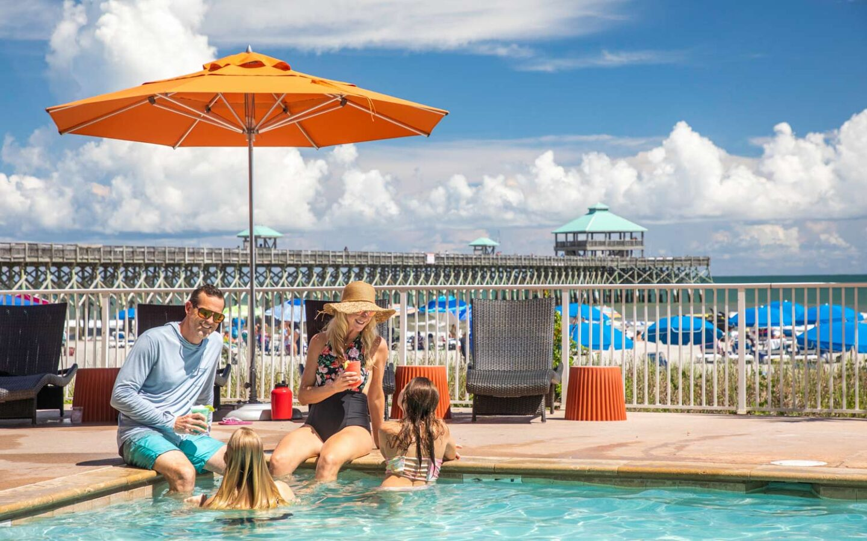 family of four sit on pools edge under orange umbrella