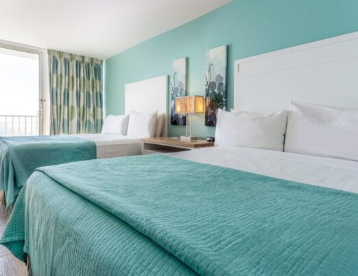 two queen double beds in a hotel room