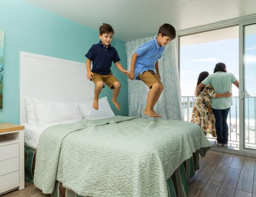 family in guest room with couple on outdoor patio and two young boys jumping on bed
