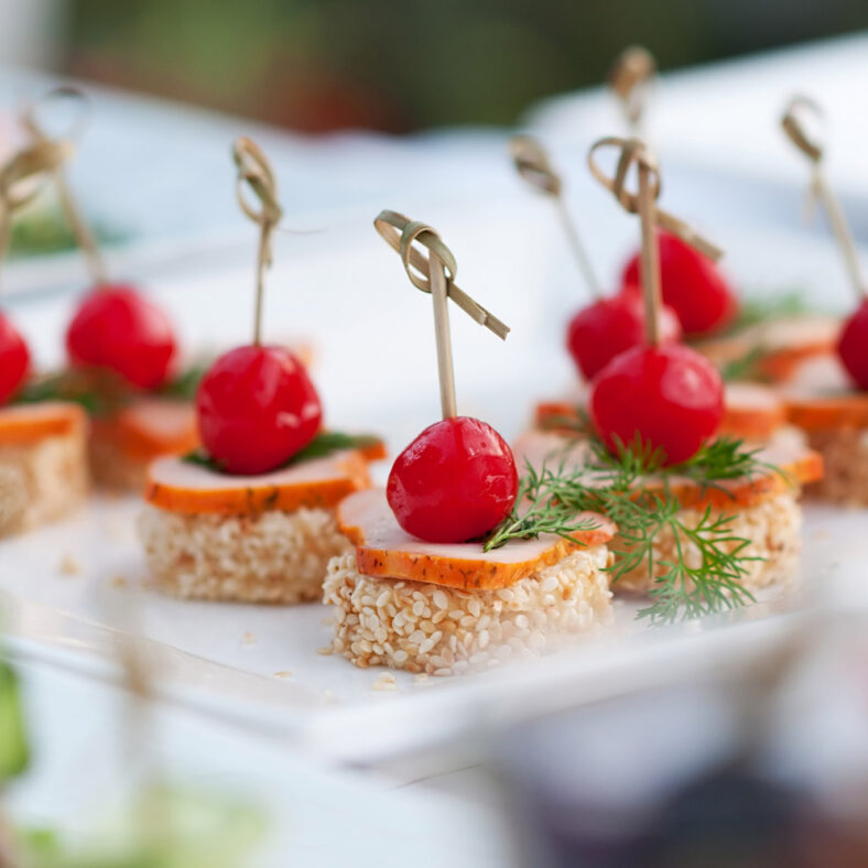 white tray of small appetizers for hosted event