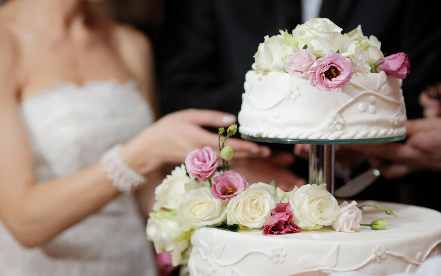 bride reaching for two tier wedding cake