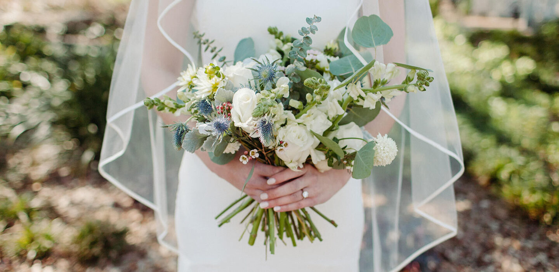 bride holding flower bouquet outside