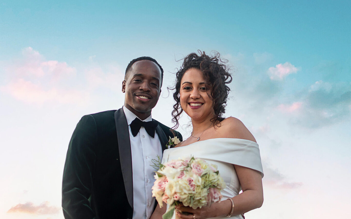 bride and groom smiling under bright blue sky