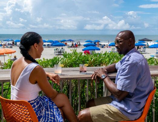 Couple enjoying drinks on BLU's tiki beach bar