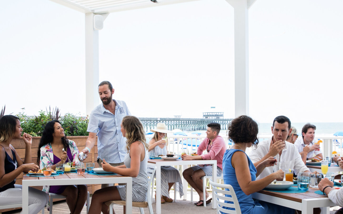 tables of diners eating on an outside beach-side pergola