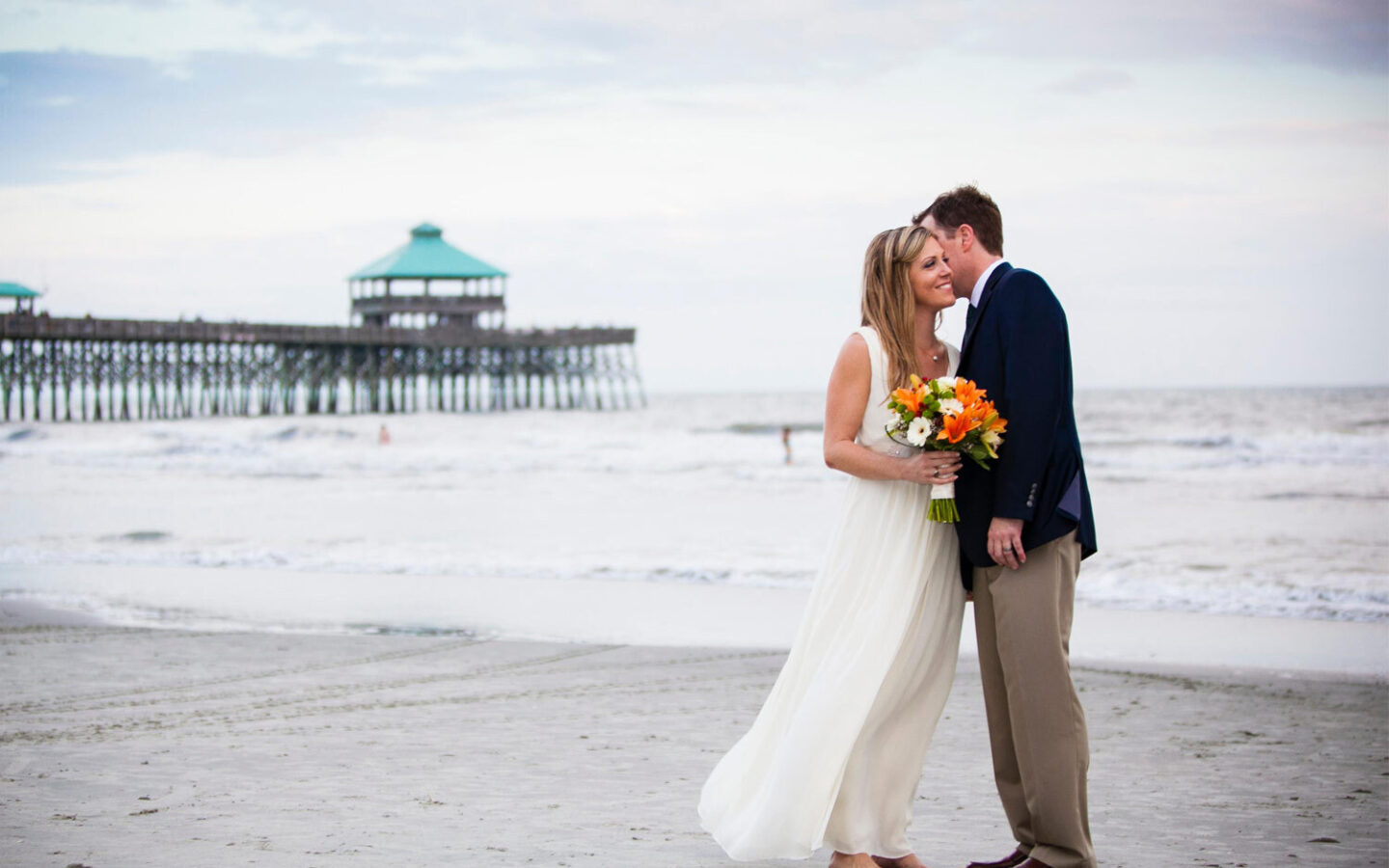 bride and groom stand on beach overlooking pier