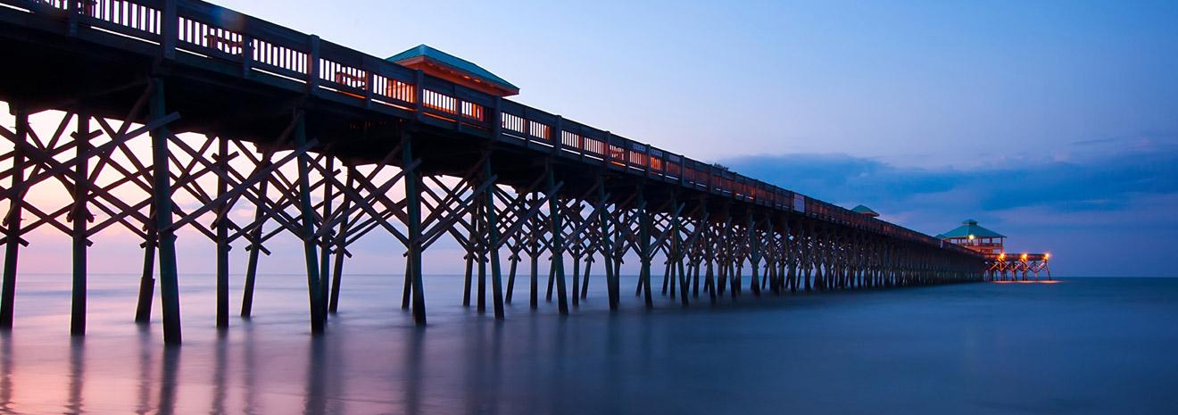long boardwalk leading to pier during dusk