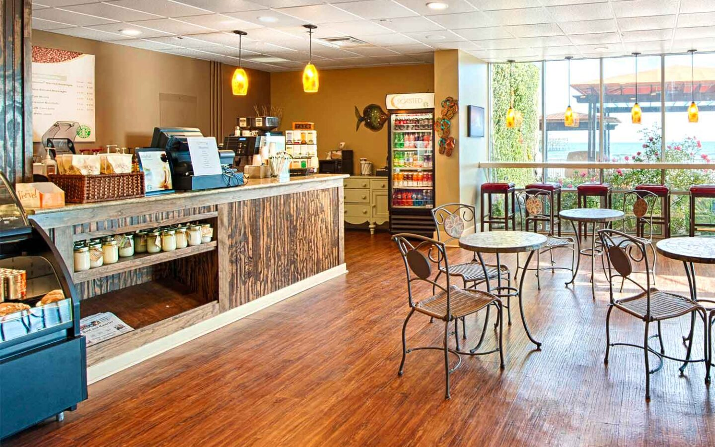 Cafe interior with long wooden table, dining tables and bar top seating