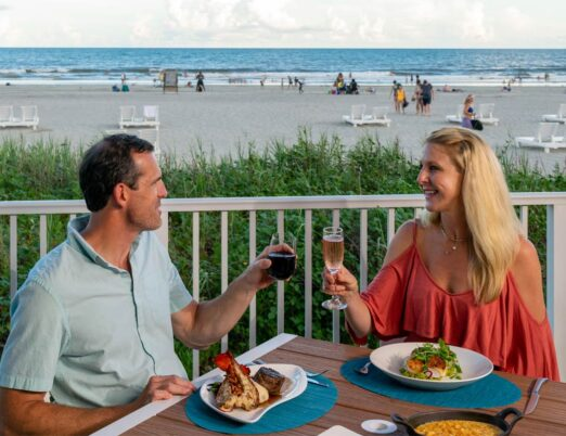 a couple dines at beach front restaurant