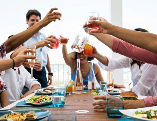 outdoor restaurant table full of dining guest holding up their glasses