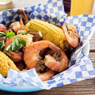 corn on the cob, potatoes and large shrimp dish