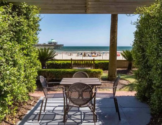 beachfront patio with four chairs and dining table overlooking beach front and pier