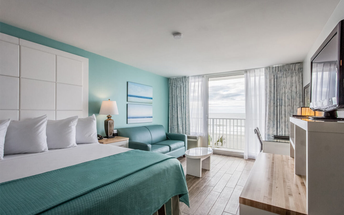 hotel room with king bed, pullout couch, and door opening to beach front view