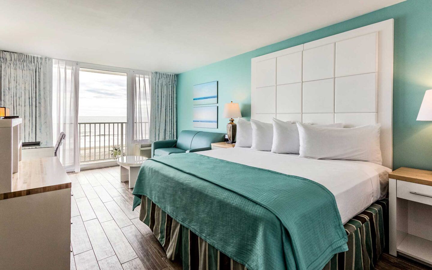oceanfront hotel room with large king bed with large patio opening to ocean view