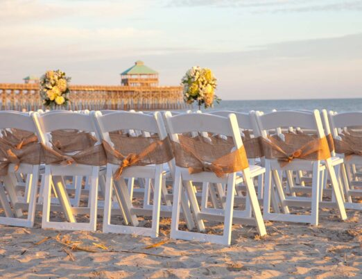 rows of white fold up wooden chairs on sandy beach prepared for wedding ceremony
