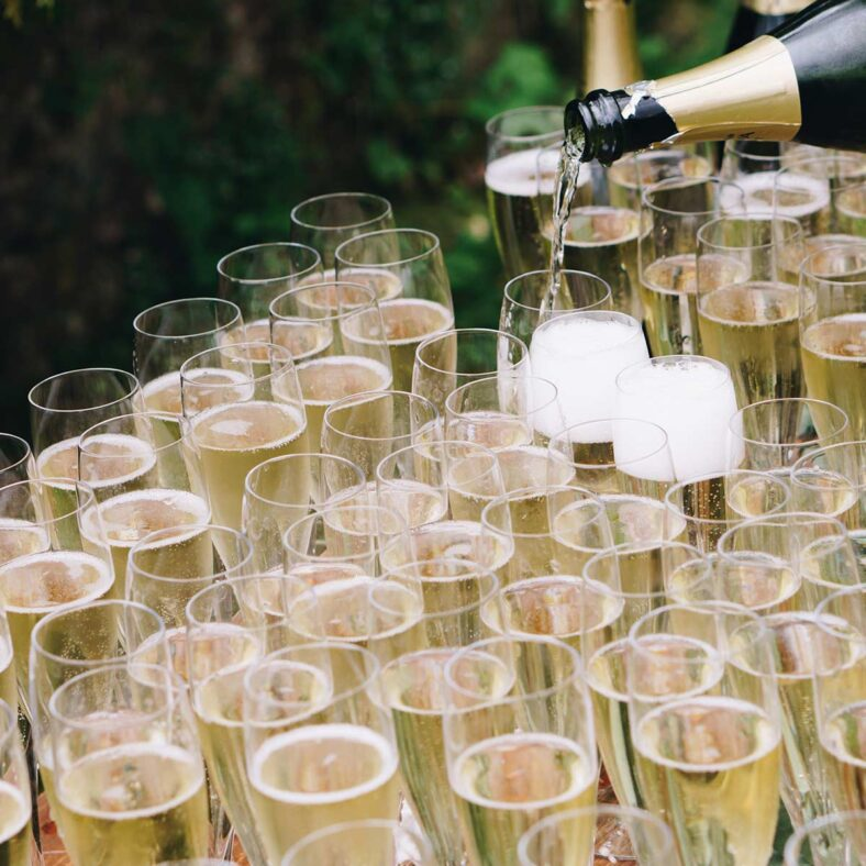 champagne being poured into many glasses outdoors
