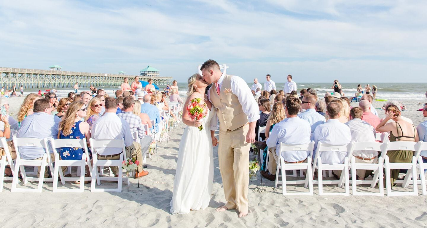 bride and groom kiss at end of the beach wedding aisle after wedding ceremony