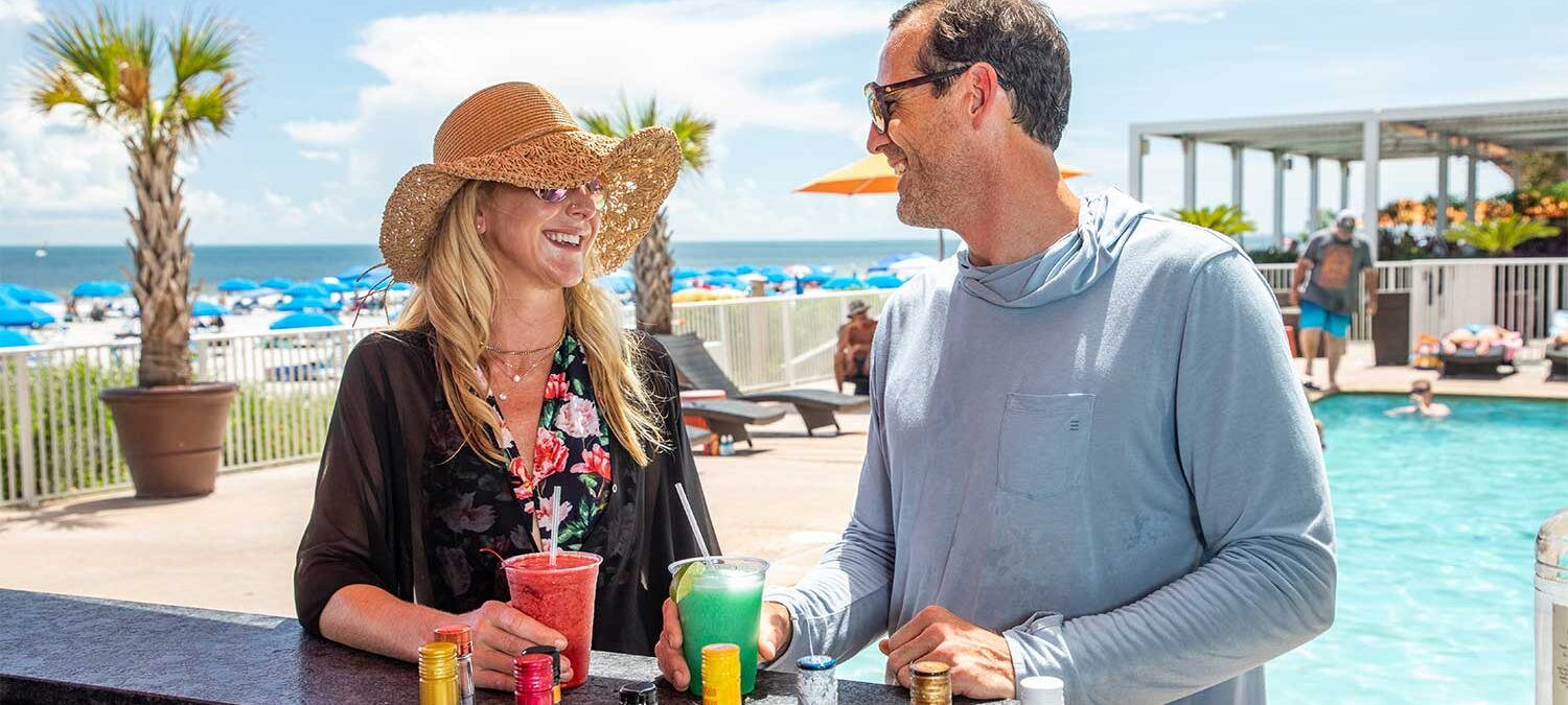 woman and man laugh with each other while holding frozen cocktails next to pool bar
