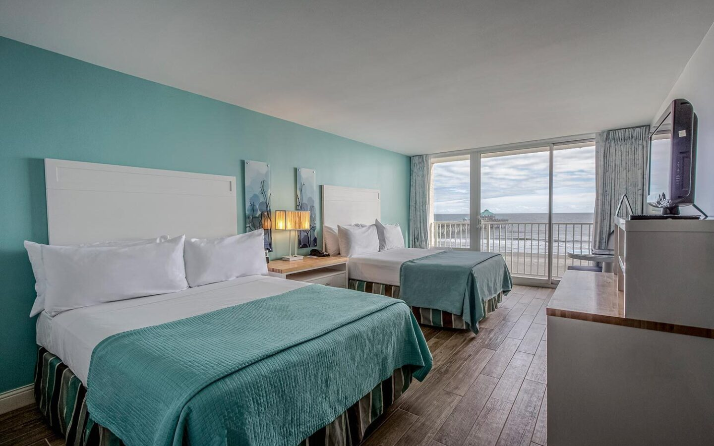 two queen double beds and side table with lamp overlooking beach front views