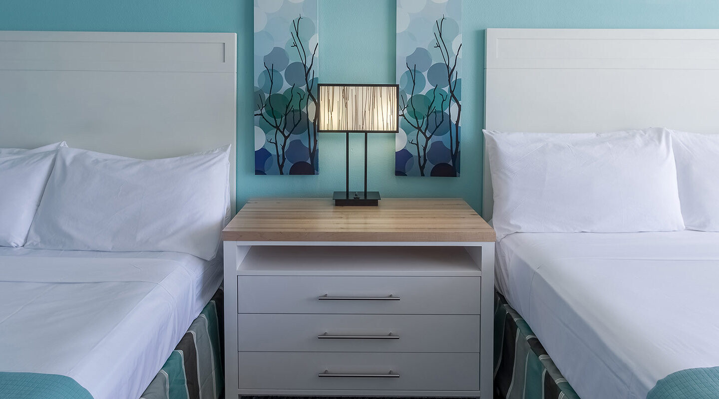 two queen double beds and side table with lamp
