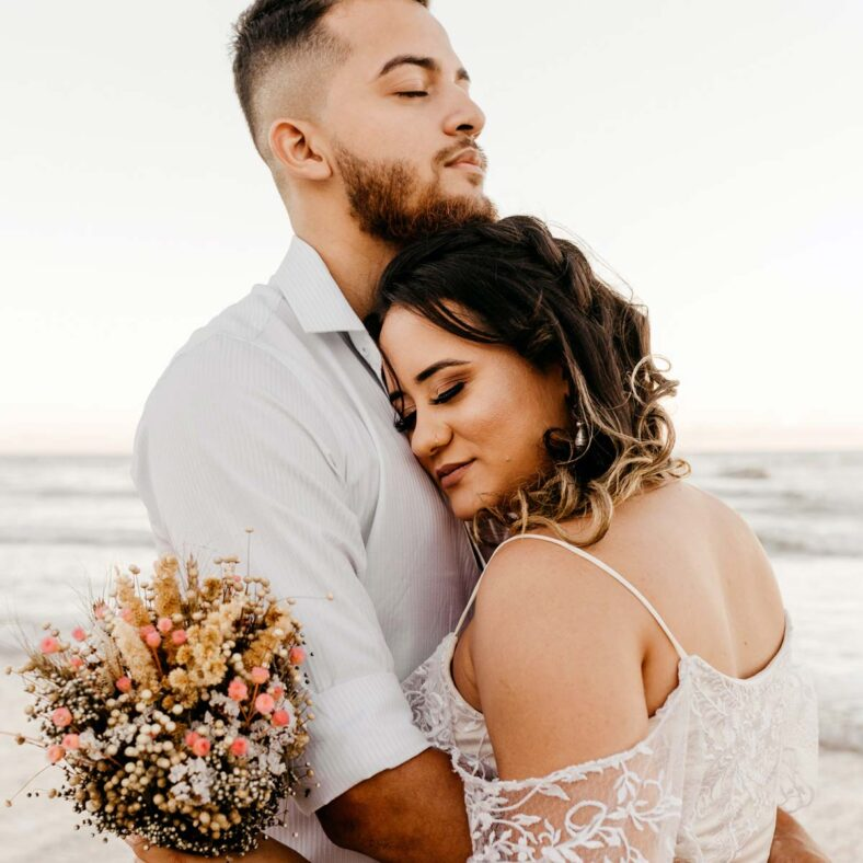 bride and groom hold each other in hug while on beach next to water