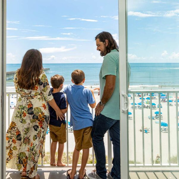 mother, father and two young boys overlook balcony view of beach