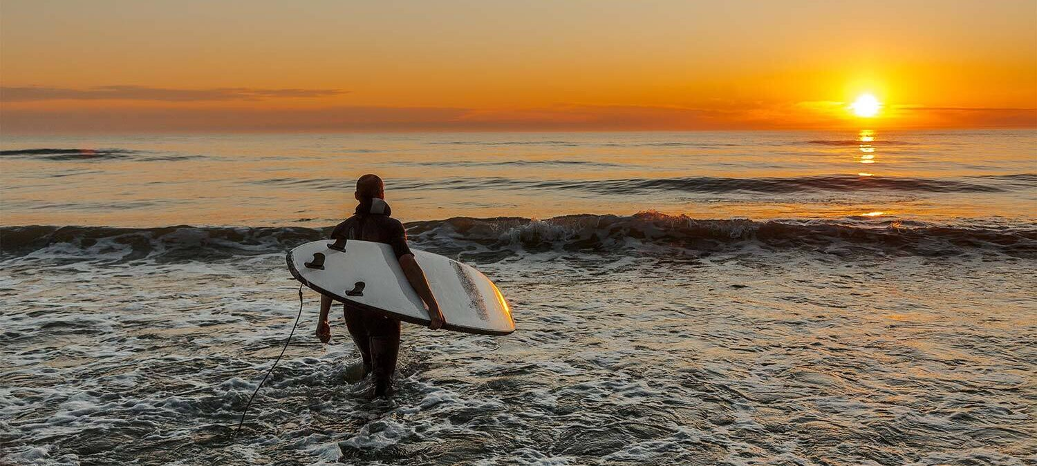 person carries surfboard into water during sunset